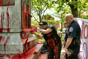 Maya Little pours her blood and red paint on Silent Sam as a cop stands over her shoulder.